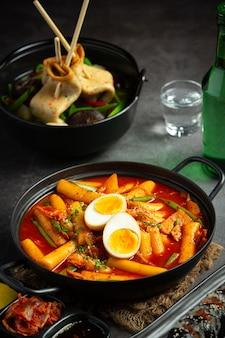 블랙 보드 배경에 치즈 tokbokki 한국 전통 음식. 점심 요리.