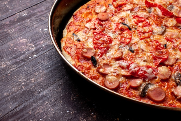 茶色の机の上の鍋の中にオリーブとソーセージが入った安っぽいトマトピザ、ピザフードミールファーストフードチーズソーセージ