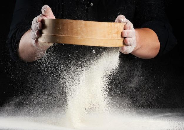 Повар мужчина в черной форме держит в руках круглое деревянное сито и просеивает белую пшеничную муку на черном