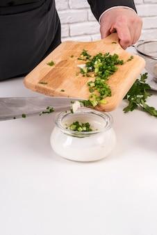 Шеф-повар добавляет зеленый лук в заправку для салата