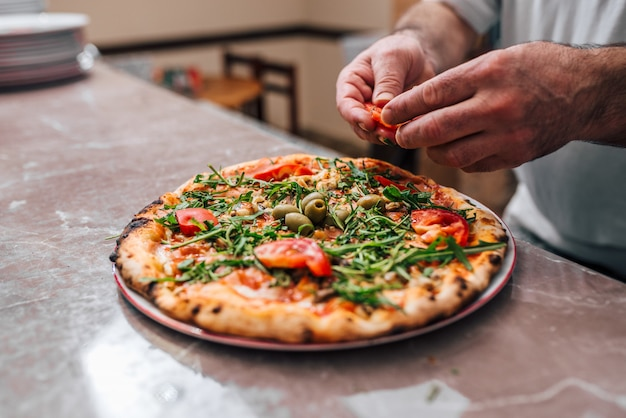 Chef adding tomatoes as a final touch on the pizza.