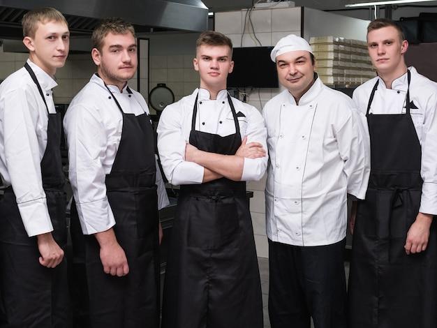 Шеф-повар и его команда профессиональных сотрудников в ресторане. работа в команде приносит успех любому бизнесу