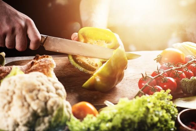 Шеф-повар на работе с овощами. концепция подлинной еды. перец, питание.