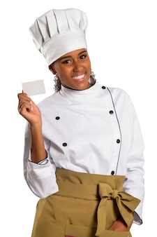 Chef, baker or cook woman showing blank sign card wearing chefs uniform and hat. blank card for menu, gift card, offer etc beautiful african / black  female isolated on white space