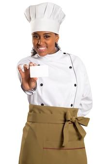 Женщина шеф-повара, пекаря или повара показывает пустую карточку знака нося форму и шляпу поваров. пустая карточка для меню, подарочной карты, предложения и т. д. красивая африканская / черная женщина, изолированная на белом пространстве
