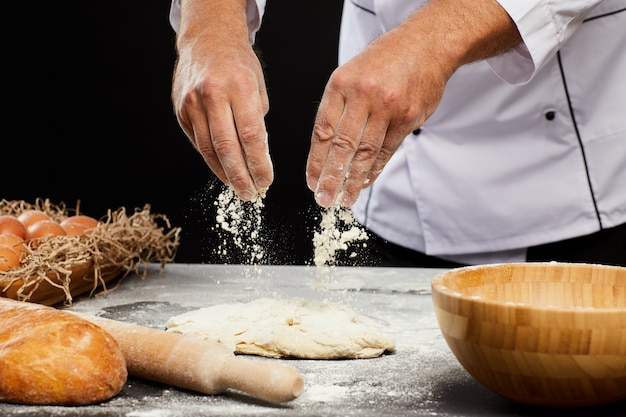 Chef baking bread against black background