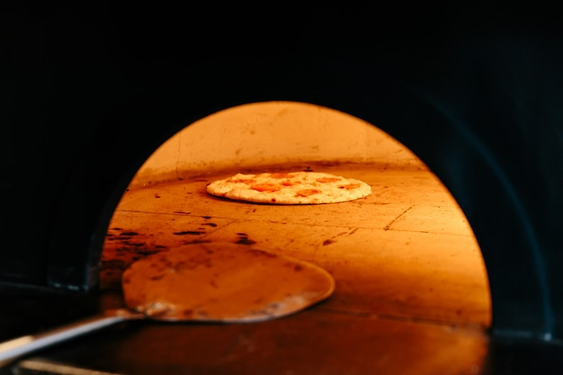 Chef baking caprese bianca pizza inside wood burning pizza oven.