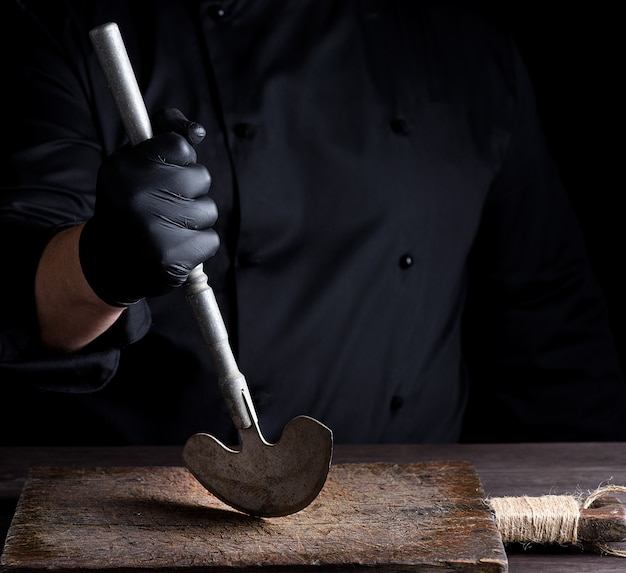 Chef in black clothes holds in his hand a metal old knife