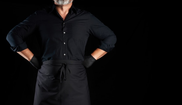 Chef in black clothes and latex gloves stands on a black background, hands on hips. place for an inscription, banner for a restaurant
