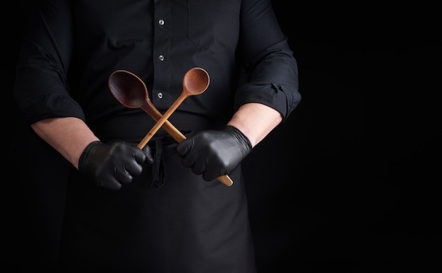 Chef in black latex gloves and a black uniform holds crossed wooden vintage spoons