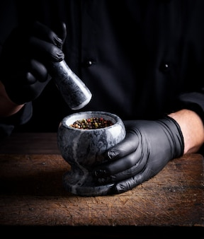Chef in black latex gloves holds a stone mortar with a mixture of peppers