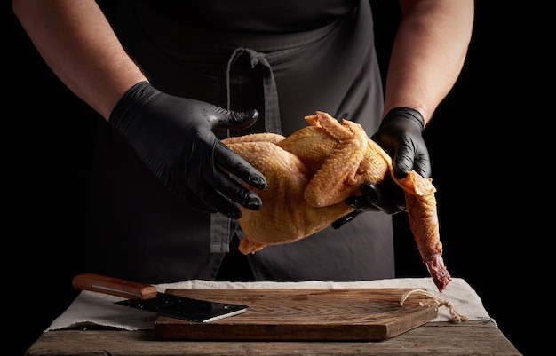 Chef in black latex gloves holds a whole chicken carcass over a brown cutting board, meat cooking process