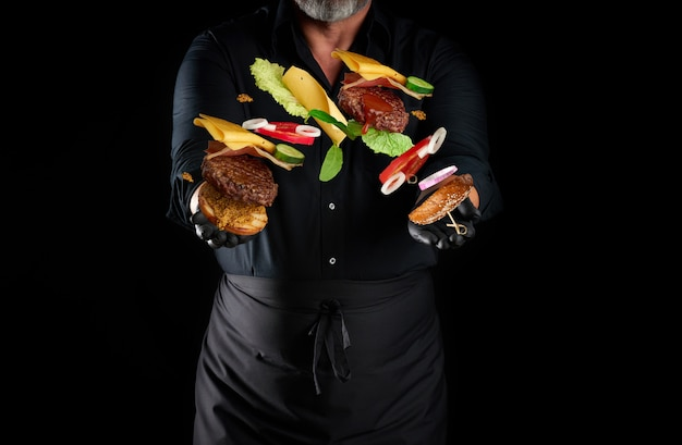 Chef in a black shirt, apron and latex black gloves stands on a black space, in his hands flying cheeseburger ingredients: a bun with sesame seeds, cutlet, tomato, lettuce and onion rings, cheese
