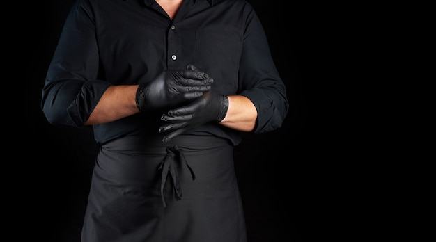 Chef in black shirt and apron puts black latex gloves on his hands before preparing food