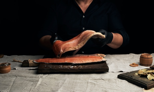 Chef in a black shirt and black latex gloves holds a large piece of salmon fish fillet over the table