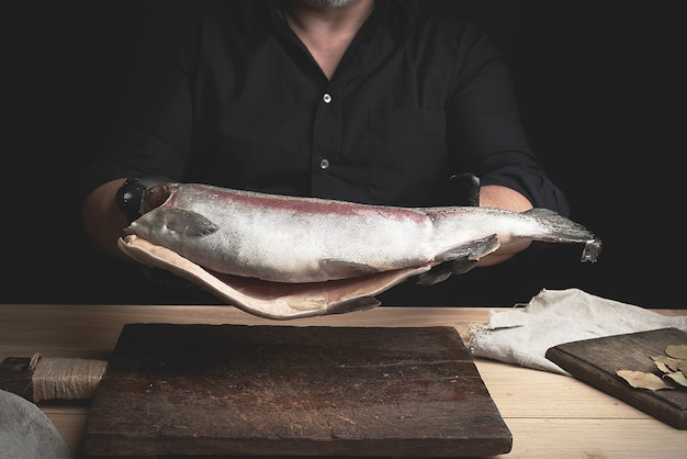 Chef in a black shirt and black latex gloves holds a raw carcass of headless salmon fish over a brown wooden cutting board