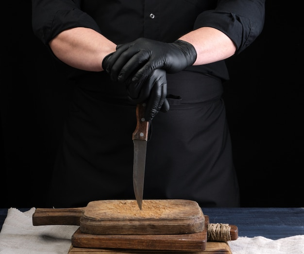 Chef in a black shirt and black latex gloves holds a vintage kitchen knife for cutting meat