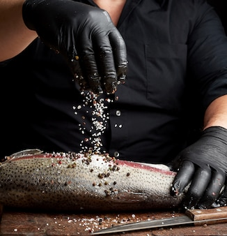 Chef in a black shirt and black latex gloves prepares salmon fillet on a wooden cutting board
