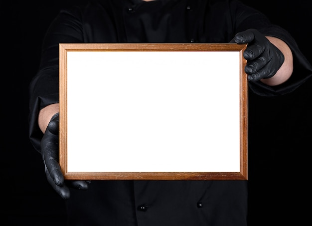Chef in black uniform and black latex gloves holding a wooden frame with white empty space