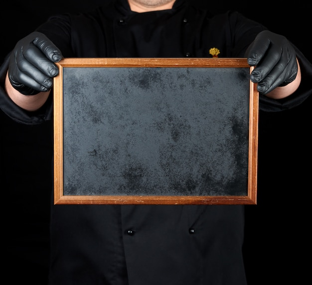 Chef in black uniform and black latex gloves holds an empty wooden frame