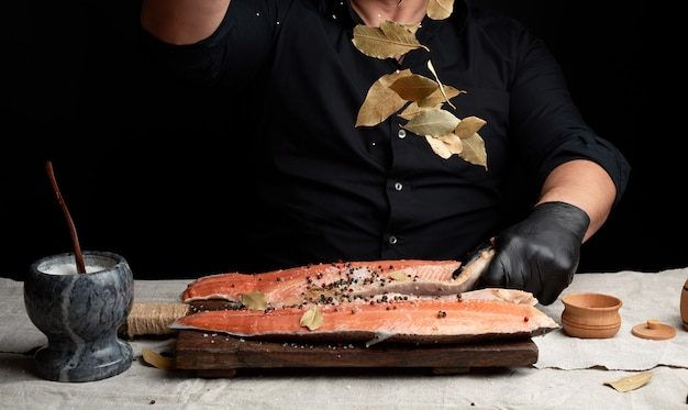 Chef in black uniform and black latex gloves pours dry leaves of bay leaf onto cut fresh salmon fillet