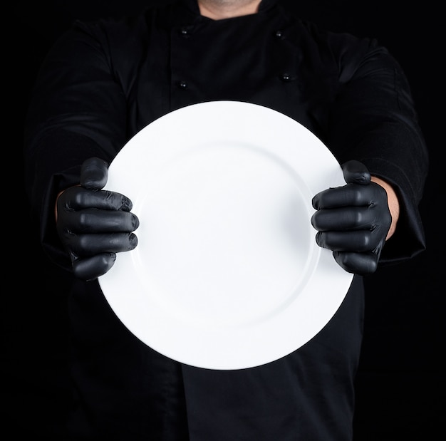 Chef in black uniform  holding a round empty plate