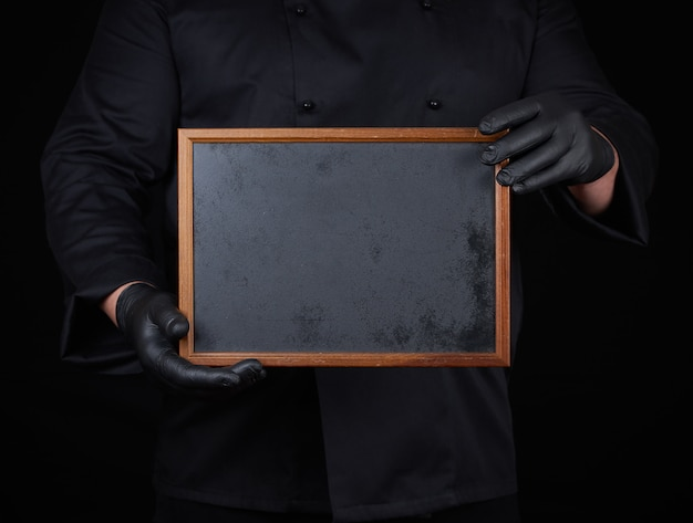 Chef in black uniform  holds an empty wooden frame