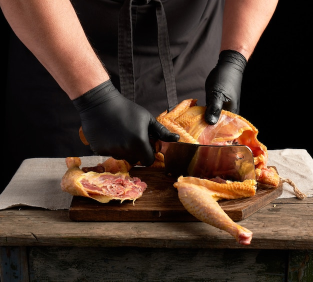 Chef in black uniform and latex gloves chopping raw chicken into pieces on a brown wooden board