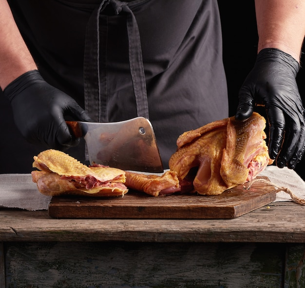Chef in black uniform and latex gloves chopping raw chicken into pieces