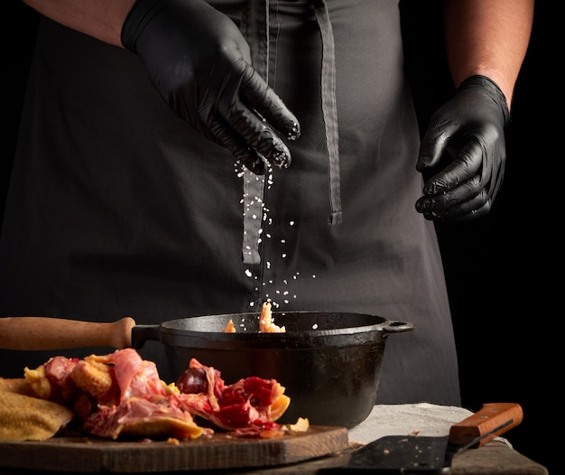 Chef in black uniform and latex gloves sprinkles with white salt raw chicken meat in a black cast iron frying pan, cooking