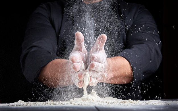 Chef in black uniform pours white wheat flour out of his hands