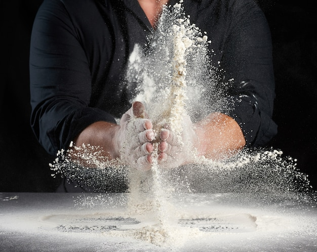 Chef in black uniform sprinkles white wheat flour in different directions, product scatters dust, black background, man sitting at a table