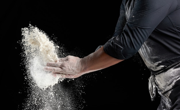 Chef in black uniform sprinkles white wheat flour in different directions