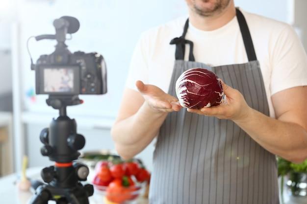 シェフのブロガーがキャベツの料理レシピを記録しています。手に熟した紫色のコールを保持しているエプロンの男。健康的な栄養ブログ。有機サラダの成分を示す男性。新鮮な野菜の水平ショット