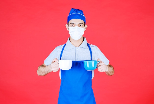 Chef in blue apron holding blue and white ceramic cups in both hands with mask on the face.