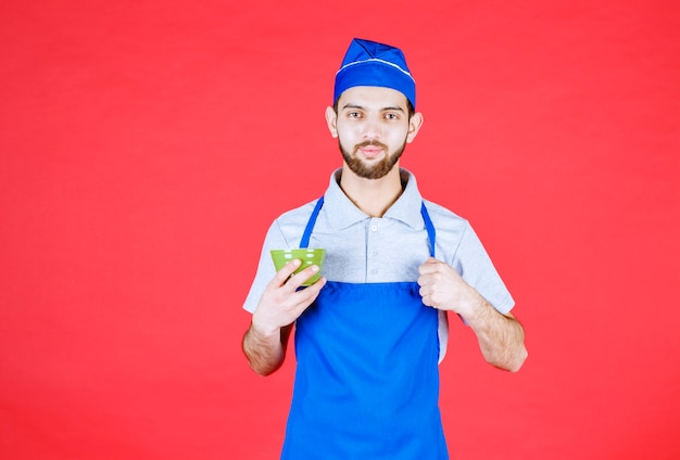 Chef in blue apron holding a green ceramic cup and showing satisfaction sign.