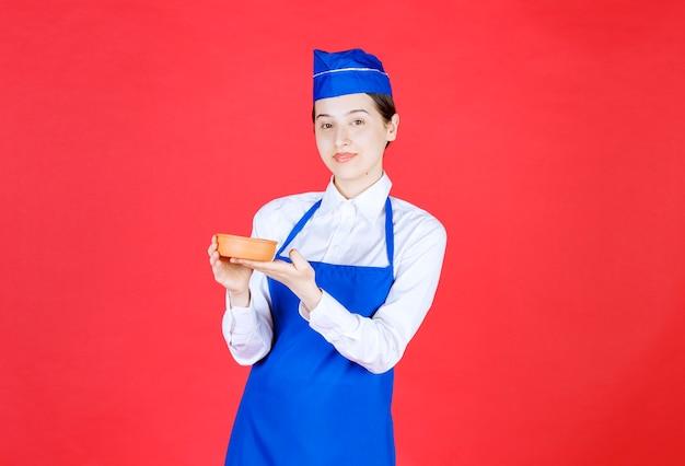Chef in grembiule blu che tiene una ciotola di ceramica.