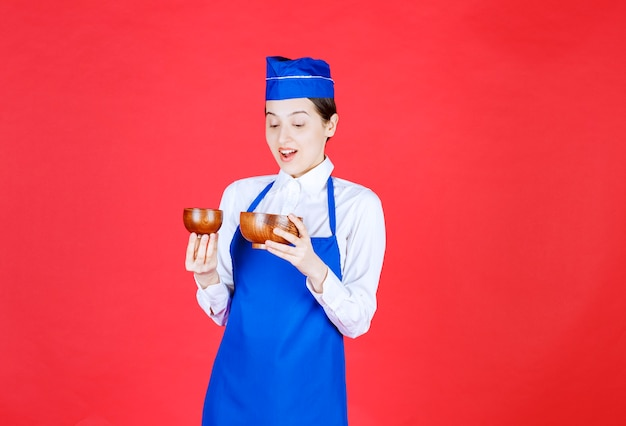 Chef in blue apron holding a pottery chinese tea cup and looks terrified and surprised.