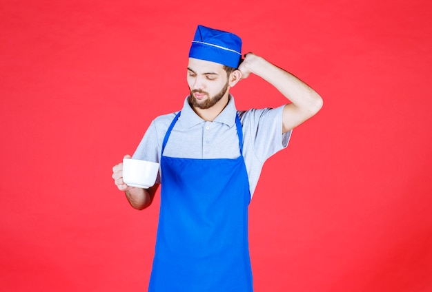 Chef in blue apron holding a white ceramic cup.