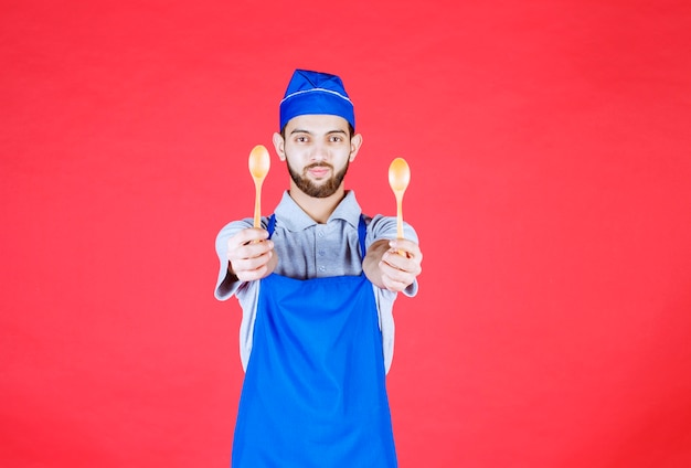 Chef in blue apron holding wooden small spoons and offering them to his colleague.
