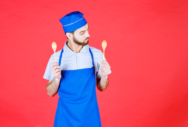Chef in blue apron holding wooden small spoons and thinking about choice.