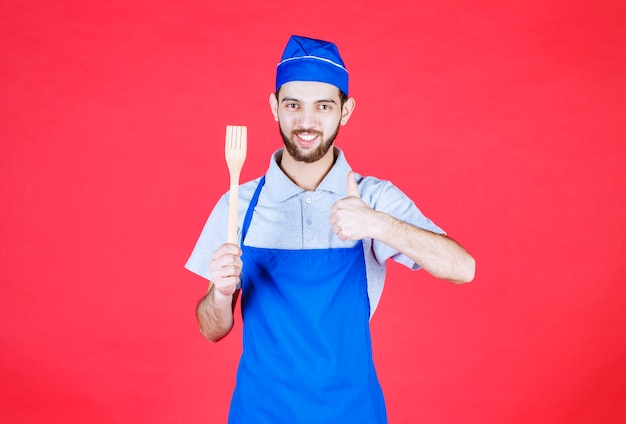 Chef in blue apron holding a wooden spatula and showing enjoyment sign.