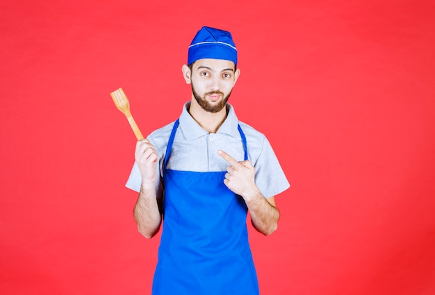 Chef in blue apron holding a wooden spatula.