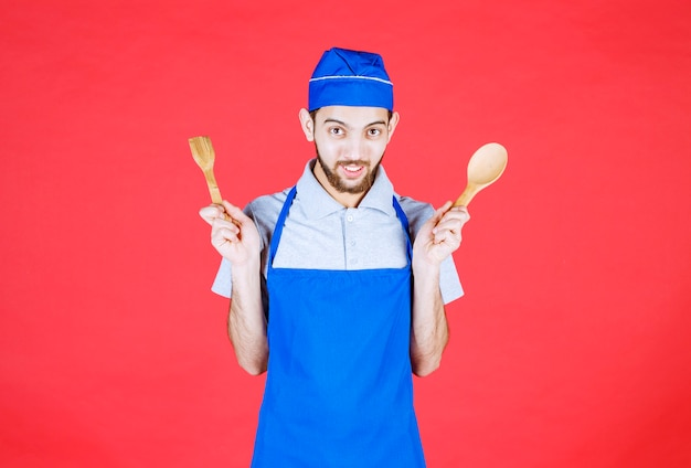 Chef in blue apron holding wooden spoon and spatula.