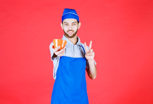 Chef in blue apron holding a yellow ceramic cup and showign enjoyment sign.