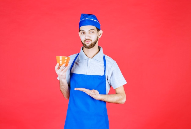 Chef in blue apron holding a yellow ceramic cup.
