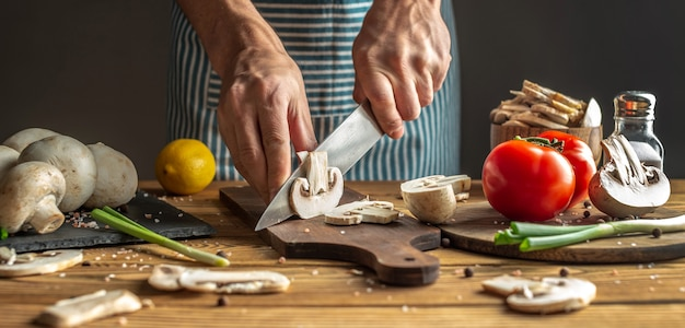 Chef in a blue apron is cutting fresh mushrooms with a knife. concept of process of cooking a delicious dish.
