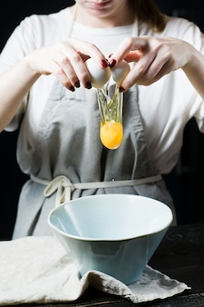 Chef breaks an egg over a bowl, cooking.