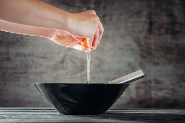 Chef breaks eggs into black bowl on wooden table
