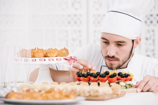 Chef carefully preparing snacks on a table